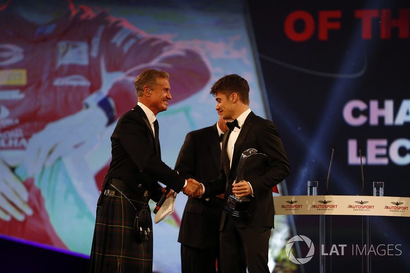 Charles Leclerc is presented with the rookie of the year award by Chase Carey, and is congratulated