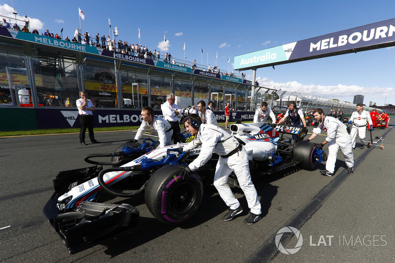 Williams engineers move Lance Stroll, Williams FW41 Mercedes, into position on the grid