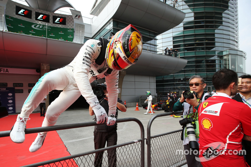 Lewis Hamilton, Mercedes AMG, scales a fence in parc ferme after taking pole position