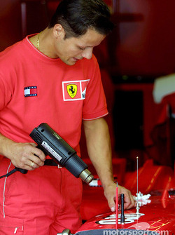 El personal del EquipoFerrari quitándole los logos de patrocinio al auto, los Ferrari competirán sin logos en Monza para compartir el duelo con el pueblo estadounidense