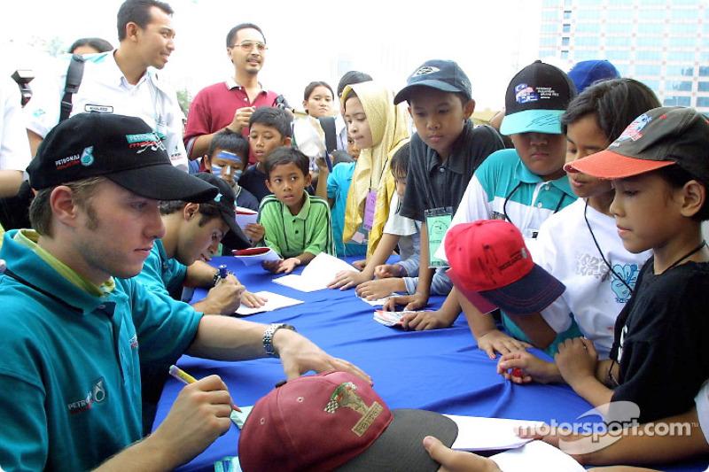 Nick Heidfeld and Felipe Massa signing autographs