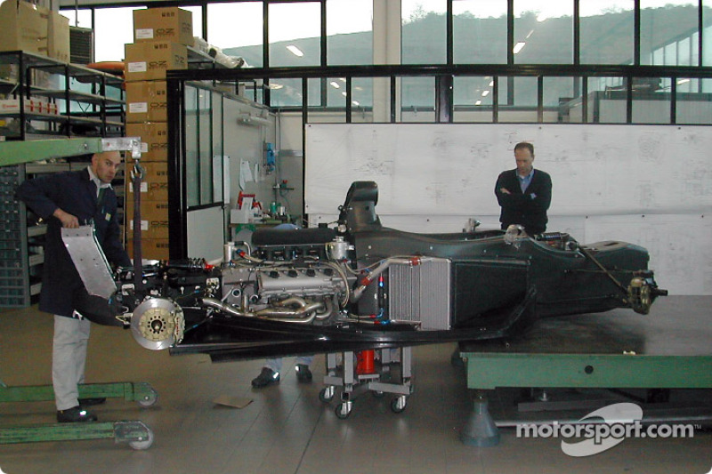Technicians install an Infiniti Q45 engine in the new Infiniti Pro Series chassis