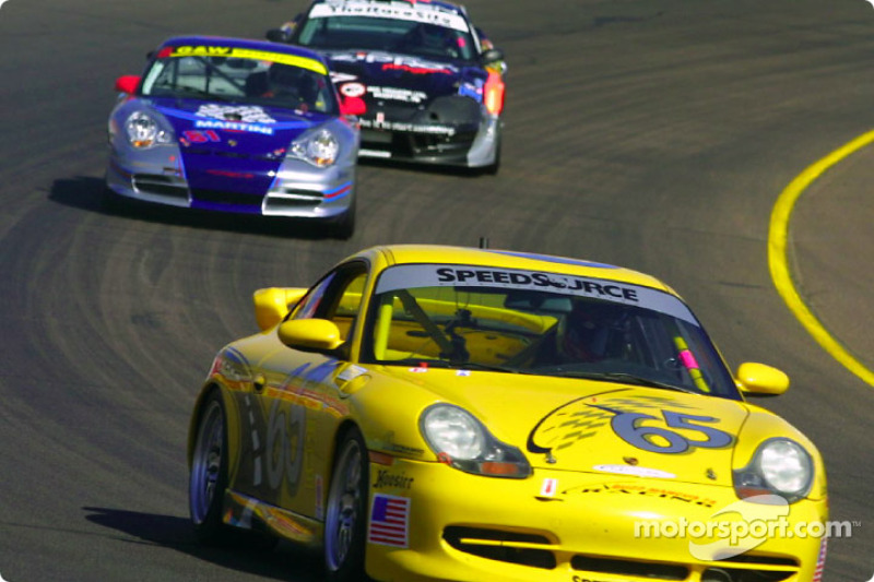 The #65 SpeedSource Porsche 911 leads a group of cars through turn four