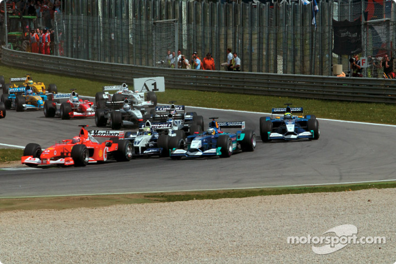 First corner: Michael Schumacher in front of Ralf Schumacher battling with Nick Heidfeld