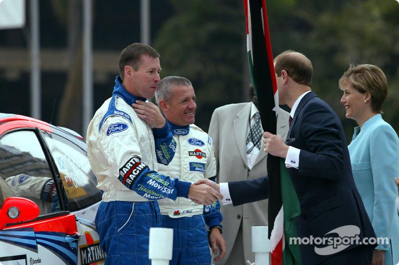Colin McRae y su copiloto Nicky Grist con el Príncipe Edward y su esposa