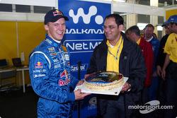 Hans-Jürgen Abt handing a birthday cake to Mattias Ekström