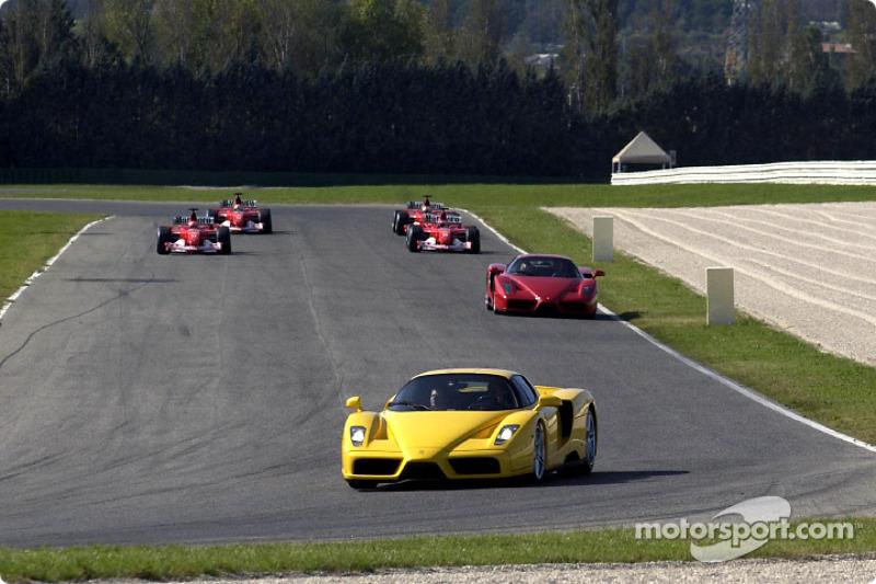 Dos Ferrari Enzo con cuatro Ferrari F2002 en la pista