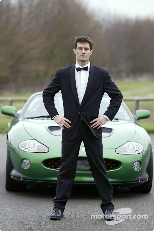 Mark Webber poses with the James Bond 007 XK-R during a photoshoot at the Jaguar Racing headquarters