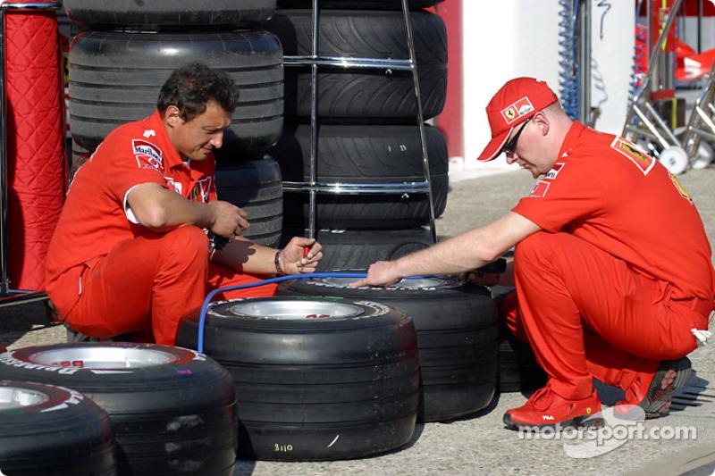 Ferrari team members prepare the tires