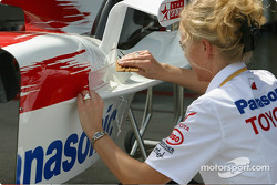 Toyota team member puts on sponsors decals