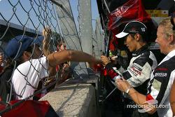 Takuma Sato firma autógrafos después de la carrera