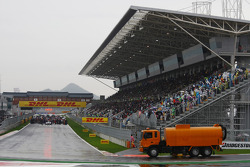 A road sweeper tries to remove some of the standing water whilst the drivers sit on the grid