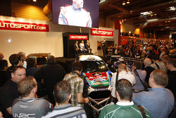 Mikko Hirvonen, Gerard Quinn and Castrol's Donald Smith on stage at the 2011 Autosport International Show in Birmingham, after the official unveilling of the all new Ford Fiesta RS WRC