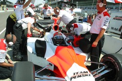 Helio Castroneves' crew converge on his car during practice