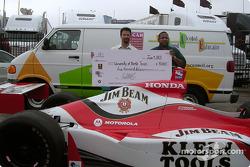 Michael Andretti presents a $5000 check to University of North Texas' health center executive director Reginald Bond