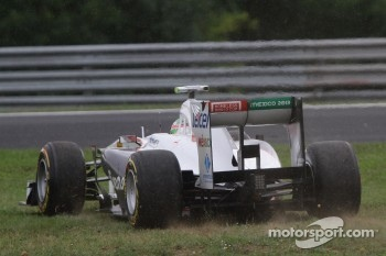 Sergio Perez takes a short cut through the slippery grass