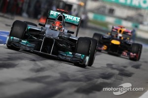 Michael Schumacher, Mercedes GP leads Sebastian Vettel, Red Bull Racing out of the pits