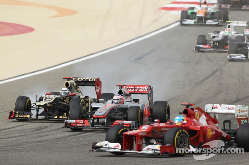 Fernando Alonso, Ferrari voor Jenson Button, McLaren en Kimi Raikkonen, Lotus bij de start van de race