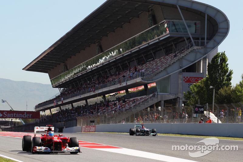 Fernando Alonso, Ferrari verlaat de pits terwijl Michael Schumacher, Mercedes AMG F1 passeert