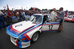 Veteran BMW racer Dieter Quester, talks to fans next to a BMW CSL