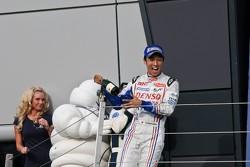 Kazuki Nakajima threatens Bibendum man and a grid girl with champagne