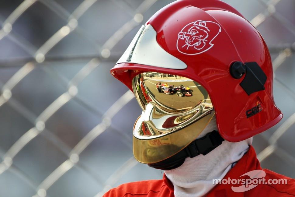 Sebastian Vettel, Red Bull Racing in the reflection of a marshall's visor