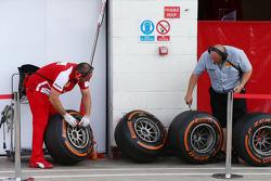 Ferrari mechanic and Pirelli tyre technician check used Pirelli tyres