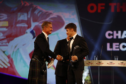 Charles Leclerc is presented with the rookie of the year award by Chase Carey, and is congratulated by David Coulthard