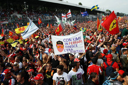 Fans celebrate under the podium with a banner for Kimi Raikkonen, Lotus F1 Team