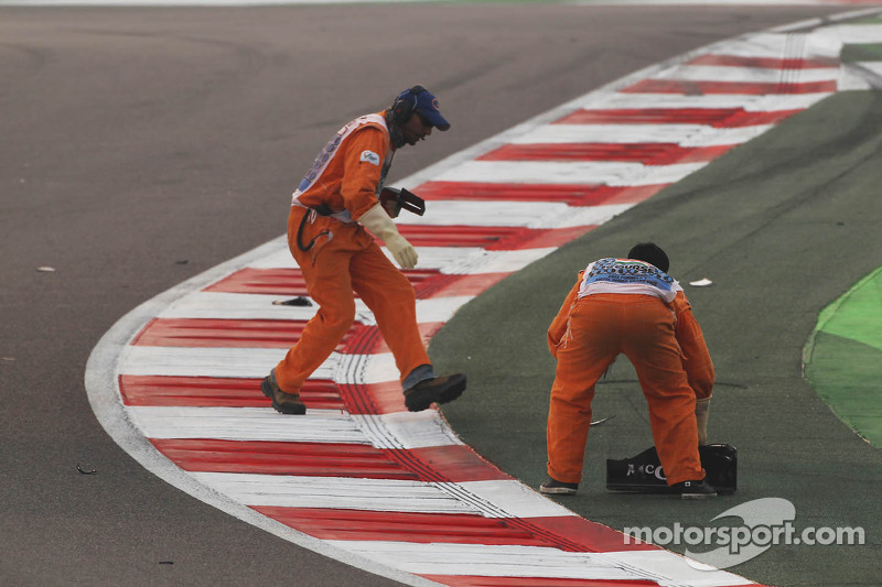 Marshals clear debris of Giedo van der Garde, Caterham F1 Team