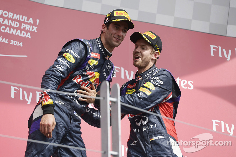 Daniel Ricciardo celebrates on the podium with team mte Sebastian Vettel