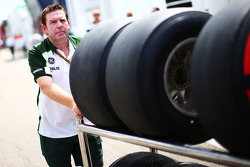 Un meccanico Caterham F1 Team spinge gli pneumatici Pirelli