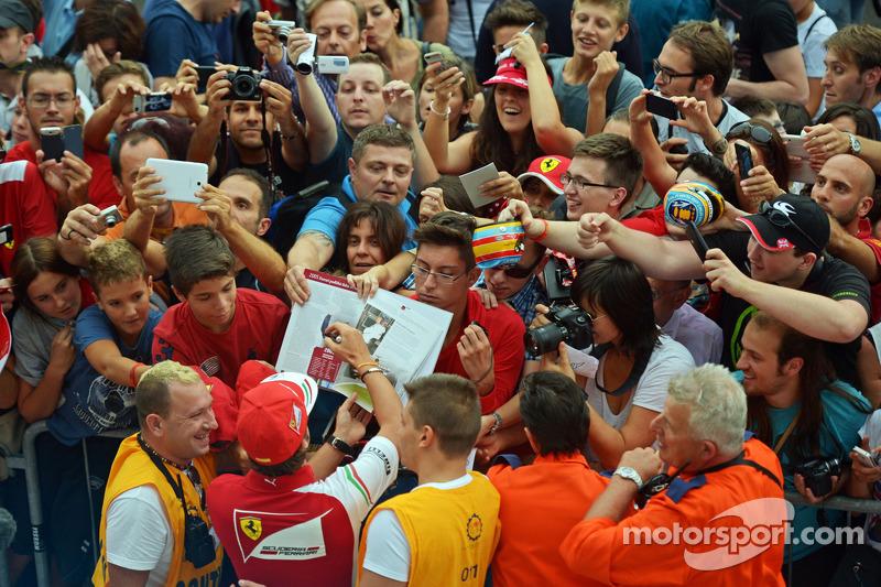 Fernando Alonso, Ferrari pit alanında taraftarlar için imza dağıtıyor
