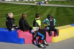 Jeunes pilotes regardant leurs idoles sur la piste