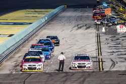 Kevin Harvick, Stewart-Haas Racing Chevrolet, Dale Earnhardt Jr., Hendrick Motorsports Chevrolet and others wait at pit exit for session restart
