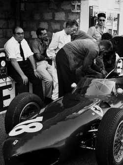 Carlo Chiti, Ferrari engine designer sitting on the pit wall with Phil Hill and Richie Ginther
