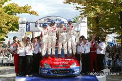 Podium: 2004 WRC champions Sébastien Loeb and Daniel Elena celebrate with Carlos Sainz and Marc Marti