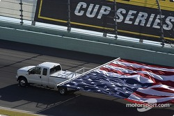 A huge American flag driven around the track