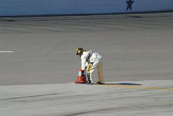 A NASCAR official sets up the pit lane cones