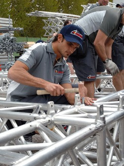 Setup of the Red Bull Energy Station and paddock area: Vitantonio Liuzzi helps the construction crew on Saturday