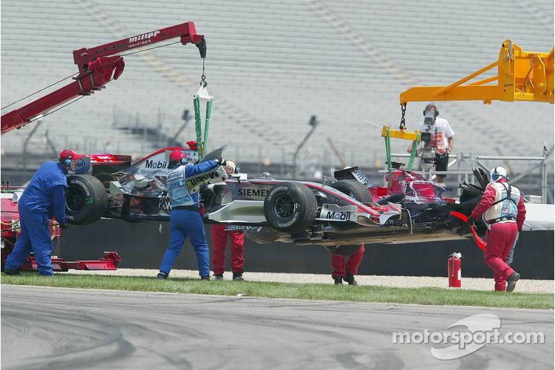 Les voitures de Kimi Räikkönen et Scott Speed sont emmenées après l'accident du premier virage