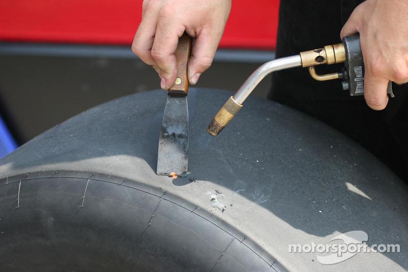 Des membres de l'équipe nettoient les pneus