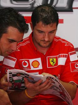 Scuderia Ferrari team members read the Red Bulletin