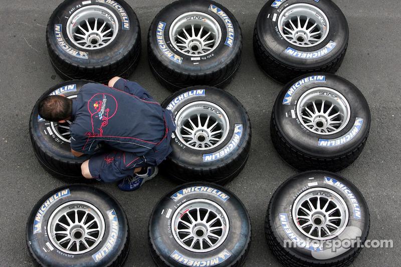 Un miembro de la tripulación con miembro del equipo Red Bull Racing tyresA comprueba los neumáticos