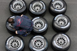 A Red Bull Racing crew member checks the tyres