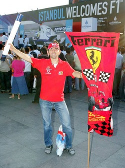 A Ferrari fan stands in front of an advertising banner in downtown Istanbul