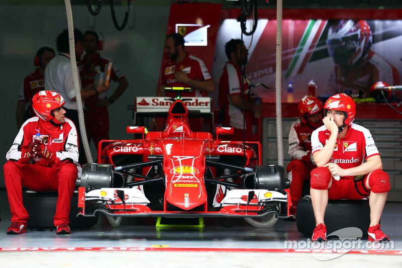Los mecánicos de sentados cerca del Ferrari SF15-T de Kimi Raikkonen, Ferrari