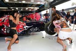 Formula Unas girl Ilaria de Santis with Scuderia Toro Rosso crew members and a photographer