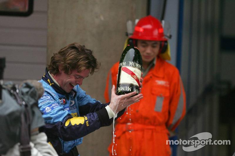 Un mecánico de Renault con una botella rota de Champaña