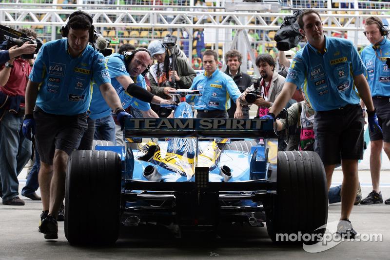 Fernando Alonso est poussé vers son garage par ses mécaniciens
